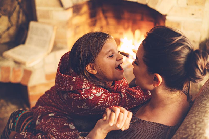 Mother and daughter cuddling by a fireplace