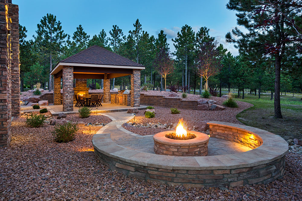 Lavish backyard featuring a firepit, covered dining area and pristine landscaping