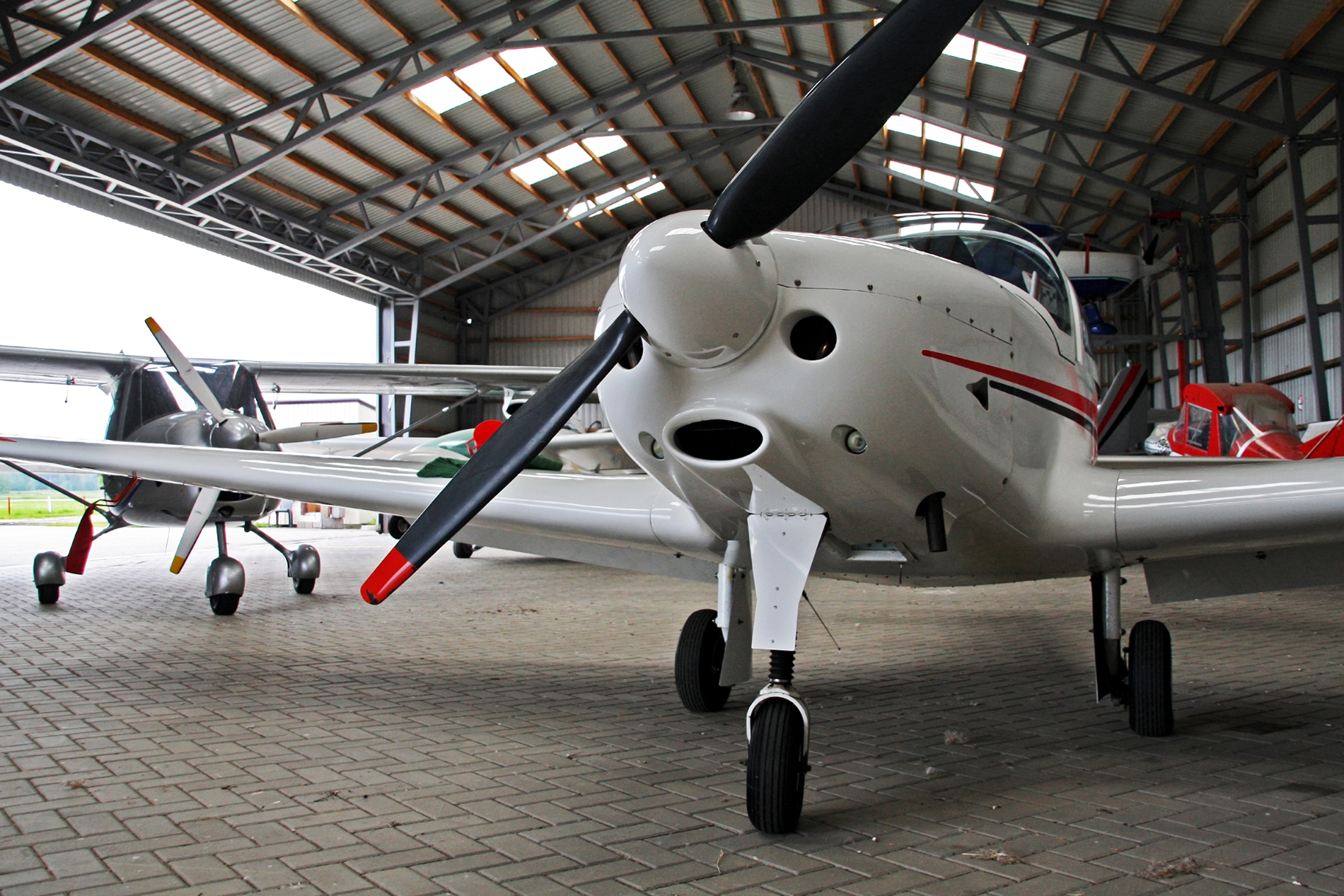 Small white plain with red trim in a hangar